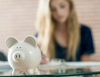 A high school teenager is writing down monthly budget in her notebook. A piggy bank is sitting on the table.